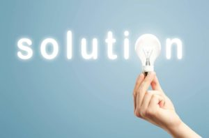 Light bulb on hand and a glowing solution word on blue background